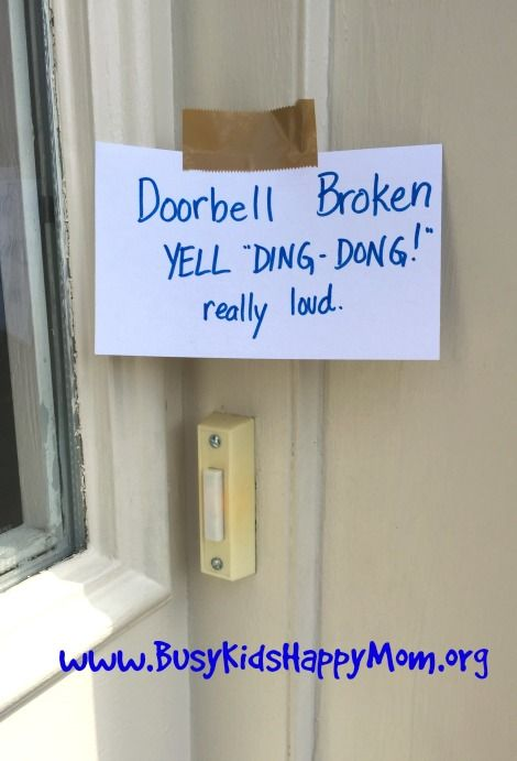 "a sign above a ""broken"" door bell"