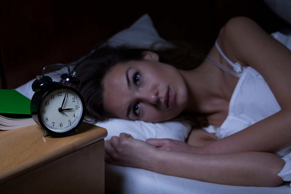 Woman with insomnia staring at a clock