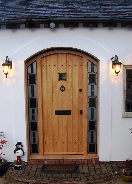 wooden front door with black iron door furniture