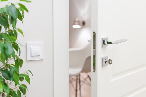 a chrome door handle on a white door